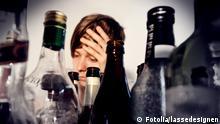 Symbolbild Alkoholismus: Viele Flaschen, dahinter ein Frauenkopf