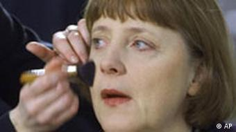 Angela Merkel getting her face made up before a TV interview