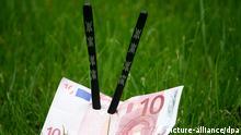 ILLUSTRATION - Ein Euroschein steckt am Montag (19.09.2011) mit zwei chinesischen Stäbchen in einer Wiese in Hamburg. China will Europa und den USA in der Krise mit neuen Investitionen zu Hilfe kommen. Foto: Daniel Bockwoldt dpa/lno