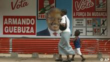 A mother and her child walk past a campaign poster showing Armando Guebuza, presidential candidate for the ruling Frelimo party, a day before the elections in Maputo, Mozambique, Tuesday, Nov. 30, 2004. Mozambique is holding parliamentary and presidential elections Dec. 1 and 2. (AP Photo/STR)