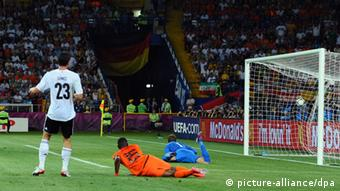 Germany's Marion Gomez (L) scores the 2-0 past the Netherlands' Jetro Willem (C) and goalie Maarten Stekelenburg during UEFA EURO 2012 group B soccer match Netherlands vs Germany at Metalist Stadium in Kharkiv, the Ukraine, 13 June 2012.