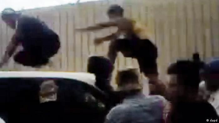 تصویری از یک فیلم ویدئو. در ۱۲ ژوئن افرادی با رفتن بر روی سقف خودروی ناظران سازمان ملل، مانع از ورود آنها به شهر حفّا در استان لاذقیه شدند. این شهر زیر بمباران شدید نیروهای نظامی قرار داشت.