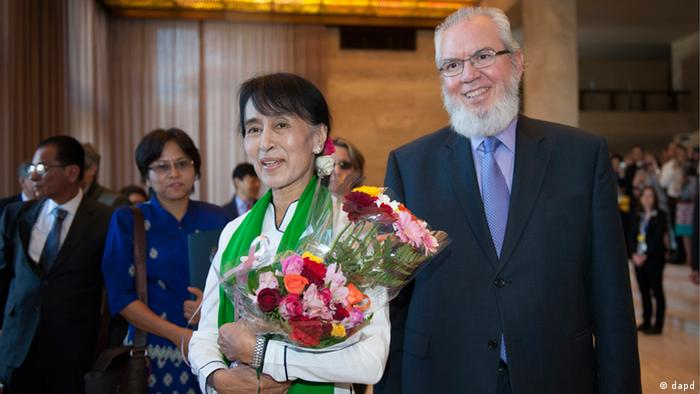 Myanmar's opposition leader Aung San Suu Kyi, left, arrives with ILO director, Chilean Juan Somavia, right, during the 101st International Labor Organization, ILO, Conference at the European headquarters of the United Nations in Geneva, Switzerland, Thursday, June 14, 2012.