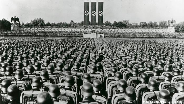 Wehrmacht soldiers parading in long rows, Nazi flags in the background ssoldaten paradieren beim Reichsparteitag der NSDAP 1934 in Nürnberg. (picture alliance / akg-images)