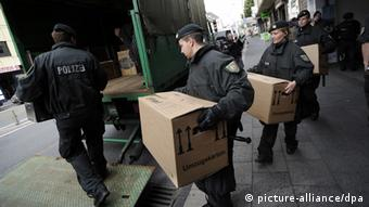 Police officers carrying boxes (photo: Henning Kaiser dpa/lnw)