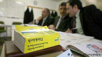Dictionaries rest in front of several people talking in an office Photo: Sebastian Widmann dpa/lno +++(c) dpa - Report+++