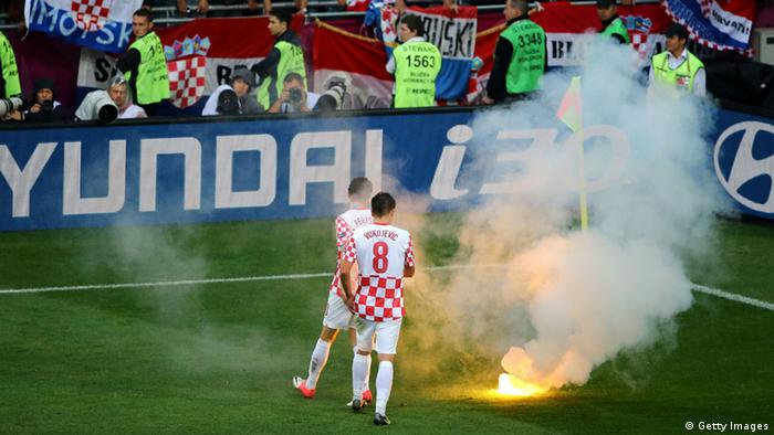 POZNAN, POLAND - JUNE 14: Ognjen Vukojevic and Ivan Perisic of Croatia look at flare that has been thrown onto the pitch during the UEFA EURO 2012 group C match between Italy and Croatia at The Municipal Stadium on June 14, 2012 in Poznan, Poland. (Photo by Christof Koepsel/Getty Images)