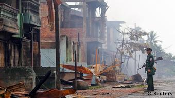 A soldier patrols through a neighbourhood that was burnt during recent violence in Sittwe
