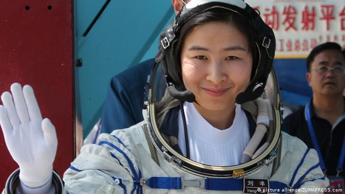 Chinese taikonaut Liu Yang, photographed in 2012, wears a spacesuit and smiles, waves
