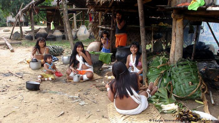 ´Mulheres e crianças indígenas sentadas no chão frente a uma cabana