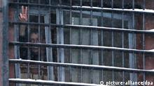 epa02509599 A man shows the 'Victory' sign from a barred window of a prison in Minsk, Belarus, in which detained participants from the 19 December protests have been held and of whom some were released on 29 December 2010. Belarusian judges had sentenced more than 600 people for taking part in massive anti-government protests after the presidential elections. A total of 580 people received jail sentences of up to 15 days each for convictions on such charges as public disorder, disobeying police instructions and damaging public property, the Itar-Tass news agency reported by citing an Interior Ministry spokesman on 21 December. EPA/TATYANA ZENKOVICH