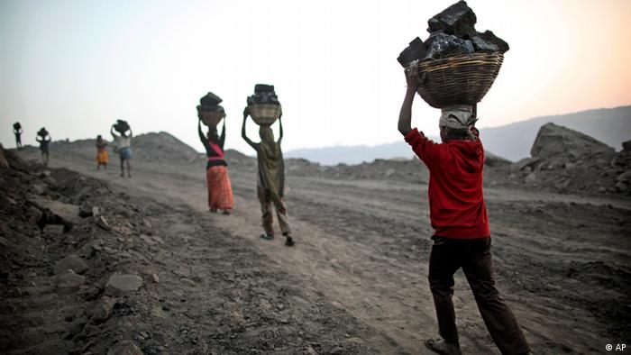 Laborers carry baskets of coal illegally from an open-cast mine in the village of Bokapahari in the eastern Indian state of Jharkhand