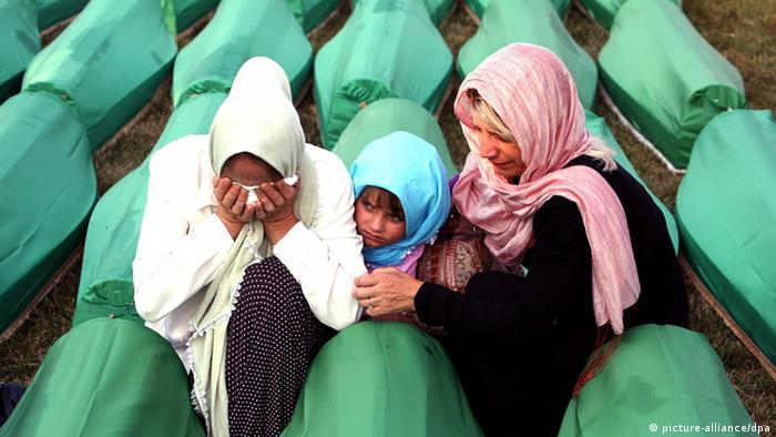 epa02819331 A Bosnian Muslim family share their grief at one of the caskets at the Potocari Memorial Center, during the funeral in Srebrenica, Bosnia and Herzegovina, 11 July 2011, where 613 newly-identified Bosnian Muslims were buried. The burial was part of a memorial ceremony to mark the 16th anniversary of the Srebrenica massacre, considered the worst atrocity of Bosnia's 1992-95 war. More than 8,000 Muslim men and boys were executed in the 1995 killing spree after Bosnian Serb forces overran the town. EPA/FEHIM DEMIR