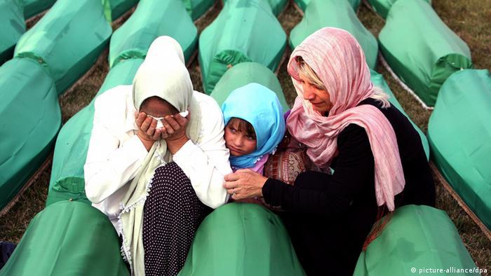 Muslimanska obitelj nad jednim od brojnih lijesova tijekom pogreba novih 613 identificiranih žrtava, Potočari 2011.