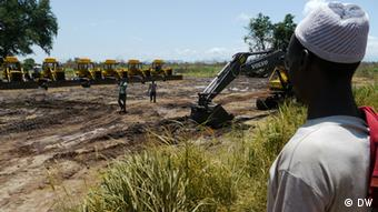 A person watching heavy equipment prepare a field Photo: Ludger Schadomsky / DW