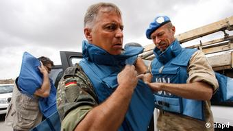 UN observers don body armor upon their arrival in Hama city, central Syria