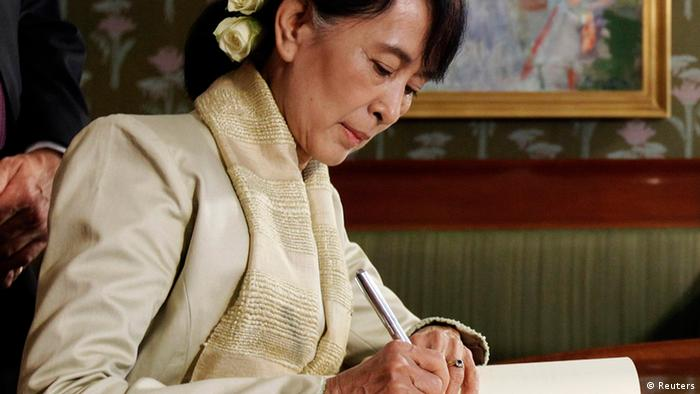 Myanmar opposition leader Aung San Suu Kyi signs a book at the Nobel Institute after a meeting with the Norwegian Nobel Committee in Oslo June 16, 2012. REUTERS/Cathal McNaughton (NORWAY - Tags: POLITICS)