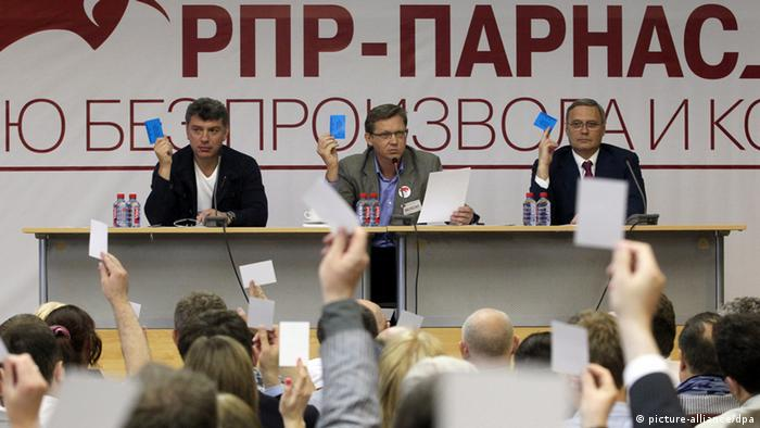 The leader of Russian People's Democratic Union, Mikhail Kasyanov (R), Russian Republican Party leader Vladimir Ryzhkov (C), and leader of Solidarnost movement, Boris Nemtsov (L), vote on the Party's new name, during the Russian Republican Party congress in Moscow, Russia, 16 June 2012.