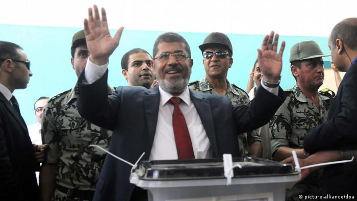 epa03267819 Egyptian presidential candidate Mohammed Morsi (C) gestures after casting his vote for the run-off presidential elections at a polling station in Sharqiya, 140 km north east Cairo, Egypt, 16 June 2012. Some 50 million people are eligible to vote in the two-day poll to pick a successor to former president Hosni Mubarak, who was deposed in a popular revolt last year. The two contenders; Muslim Brotherhood candidate, Mohammed Morsi, and Mubarak's last PM, Ahmed Shafik, failed to secure an outright majority in the first round last month. EPA/STR