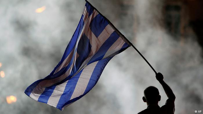 An elderly supporter of New Democracy party waves a Greek flag in front of a smoke from flairs during an election rally at Syntagma square in Athens, Friday, June 15, 2012. Greeks cast their ballots this Sunday for the second time in six weeks, after May 6 elections left no party with enough seats in Parliament to form a government and coalition talks collapsed. (Foto:Petros Karadjias/AP/dapd)