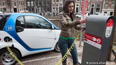 A woman charges an electric car in Amsterdam