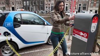 Женщина подзаряжает электромобиль