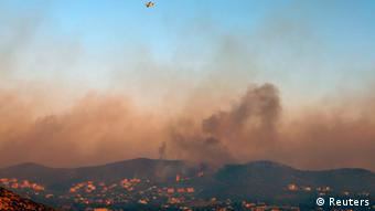 A firefighting plane flies over a forest fire at Thymari coastal village, 40 km (25 miles) southeast of Athens, June 16, 2012. REUTERS/Yannis Behrakis (GREECE - Tags: DISASTER)