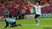 Germany's Lars Bender (L) celebrates with team mates Mesut Oezil and Miroslav Klose (R) after scoring against Denmark during their Euro 2012 Group B soccer match at the New Lviv stadium in Lviv, June 17, 2012. REUTERS/Eddie Keogh (UKRAINE - Tags: SPORT SOCCER)
