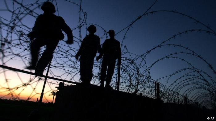 Egyptian soldiers walk along a border wall
