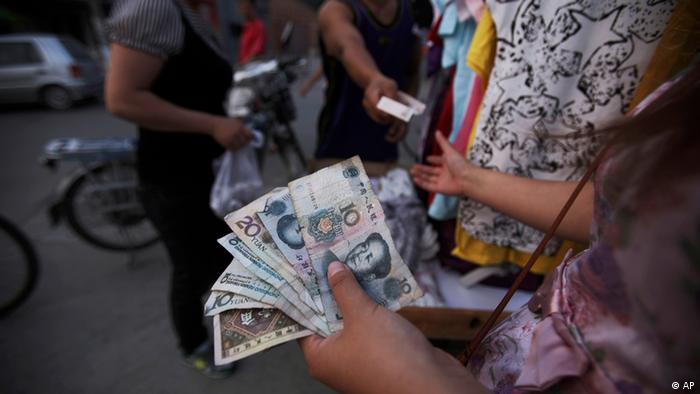 A Chinese woman, who sells clothes on the roadside, holds tens of Yuan, while dealing with a customer, in a Hutong, or a traditional alleyway, in Beijing, China, Tuesday, June, 22, 2010. (Foto: AP)