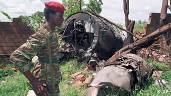 A soldier looks at the wreckage of the plane in which Juvenal Habyariman died. (AP Photo / Jean-Marc Bouju, Archiv)