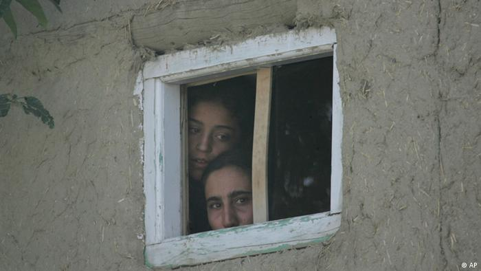 Women peer out of a window to look at the scene after a suicide attack in Kabul, Afghanistan, Friday Aug. 31, 2007. A suicide attacker detonated his vehicle close to the airport in the Afghanistan capital on Friday, killing at least one solider and wounding six others, officials and witnesses said. (AP Photo/Saurabh Das)