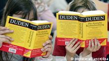 صورة رمزية لطفلين بيدهما نسخة من قاموس دودن الألماني للكتابة الصحيحة لمفردات اللغة الألمانية.