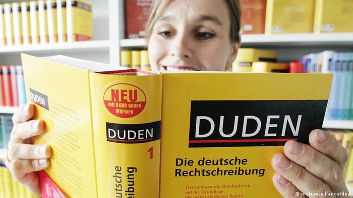 Eine Frau liest im Duden.