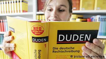 Eine Frau liest in einem Duden