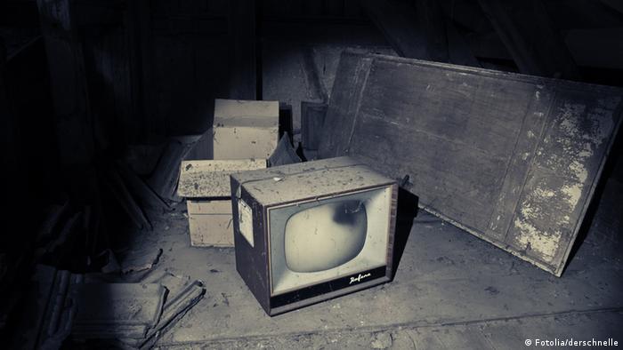 Das Bild zeigt einen verstaubten Fernseher auf einem Dachboden