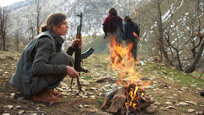 Helal Kurdistany, a member of the Kurdistan Workers' Party, or PKK, warms herself by the fire at their camp in the Qandil mountains near the Turkish border with northern Iraq