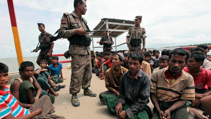 Rohingya Muslim men, fleeing from ethnic violence in Myanmar between Buddhists and minority Rohingya Muslims, are kept under guard after they are brought by Bagladeshi border guards to a boat jetty at Shahporir Dwip in Taknaf, Bangladesh, Monday, June 18, 2012