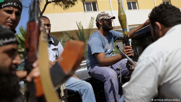 Rebellen sitzen am Mittwoch (24.08.2011) auf einem Stützpunkt in Tripolis auf einem Pickup und warten auf einen Einsatz. Das Regime des libyschen Diktators Gaddafi ist am Ende, doch trotz der Siegesfeiern der Rebellen kämpfen seine letzten Getreuen erbittert gegen den Untergang. In Tripolis und anderen Orten Libyens lieferten sich Aufständische und Gaddafis Truppen am Mittwoch weiterhin teils schwere Gefechte. Foto: Hannibal dpa/lbn pixel