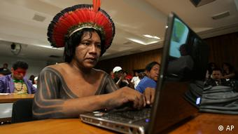 Indigenous person in traditional dress using a laptop
