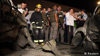 Israeli security forces stand at the scene where a rocket fired from Gaza exploded inside a border police base in south Israel June 19, 2012