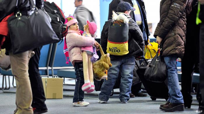 Christian refugees from Iraq at the airport in Hanover, Germany, wait to be transported to the border transit camp