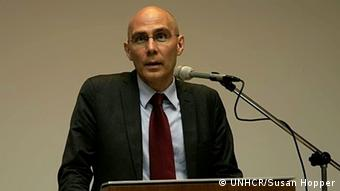 UNHCR's Volker Türk, giving a speech, standing at a podium behind a microphone.