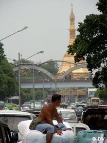 A person rides a bike on a busy street in Yangon