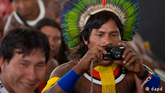 An indigenous man takes a picture during the People's Summit for Social and Environmental Justice in defense of the commons, a parallel event taking place alongside the United Nations Conference on Sustainable Development, or Rio+20, in Rio de Janeiro, Brazil, Friday, June 15, 2012. (AP Photo/Silvia Izquierdo)