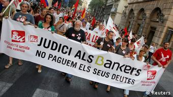 Protestors march during a demonstration against cuts in public services in central Valencia June 20, 2012. The banner reads Trial for the bankers, we won't pay their debts. REUTERS/Heino Kalis (SPAIN - Tags: POLITICS CIVIL UNREST)