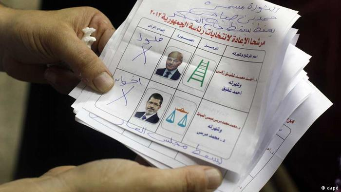An Egyptian elections official holds unusable ballots at a polling center after the second day of the presidential runoff, in Cairo, Egypt, Sunday, June 17, 2012. As Egyptians voted in a second day of elections for a successor to Hosni Mubarak, the ruling military issued an interim constitution Sunday defining the new president's authorities, a move that sharpened the confrontation with the Muslim Brotherhood and showed how the generals will maintain the lion's share of power no matter who wins. The Arabic handwriting from top to bottom reads revolution will continue, Hamdeen Sabahi, down with military rule, remnants of old regime, brotherhood. The Arabic in print reads presidential runoff candidates 2012, Ahmed Shafiq, at top, and Mohammed Morsi. (Foto:Amr Nabil/AP/dapd) // Eingestellt von wa