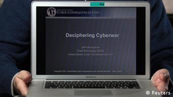 A person holding a laptop computer with the words Decipherine Cyberwar on the monitor Photo: REUTERS/John Adkisson/Files
