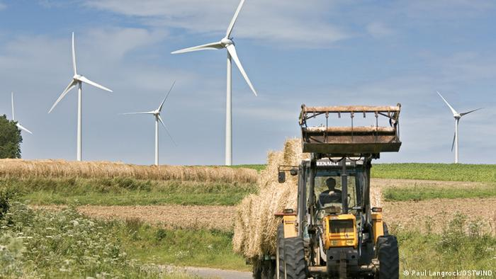 Tractor works in front of wind farm in Germany (Quelle : PaulLangrock / Ostwind) Alle Windparks sind in Deutschland. Unter den Dateien stehen die Namen der Windparks. Verwendung nur Berichterstattung Ostwind