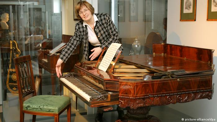 Museum Director Eszter Fontana displays a piano that doubles as a table